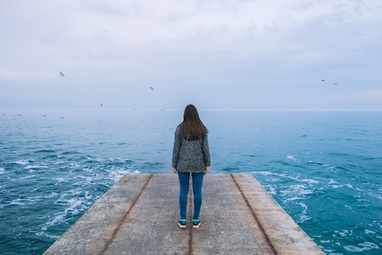 Image of a woman on a dock facing the ocean