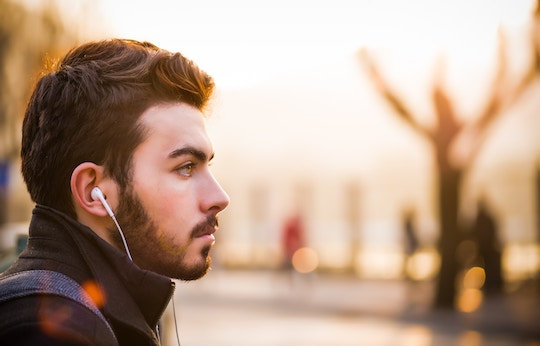 Image of a man listening with ear buds