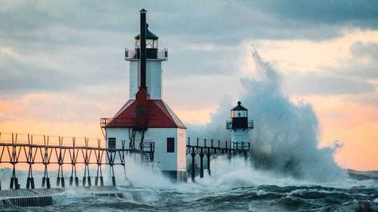 Image of a lighthouse battered by huge waves