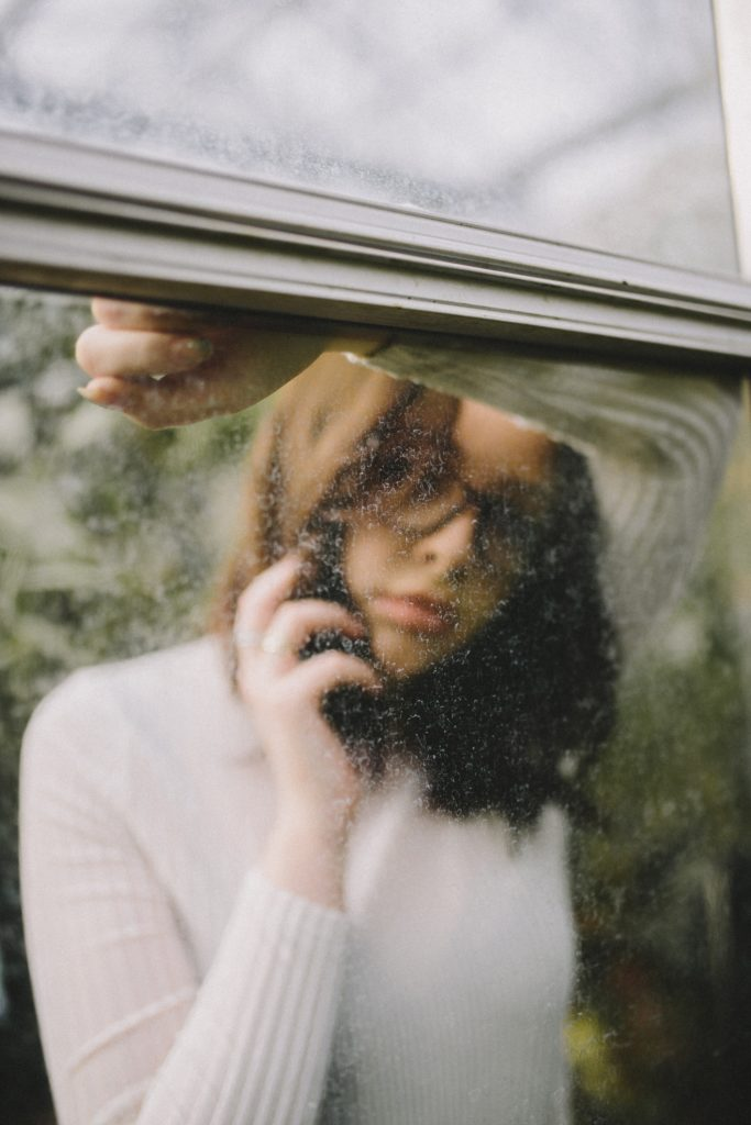 Woman looking through a Dirty Window