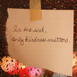Rainy window with a note stuck on about kindness