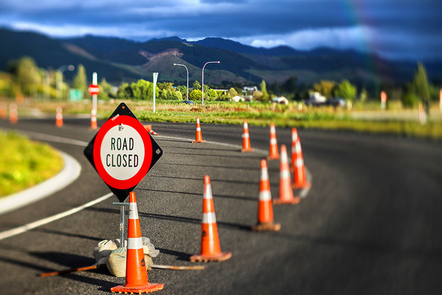 Image of orange construction cones on a curved road