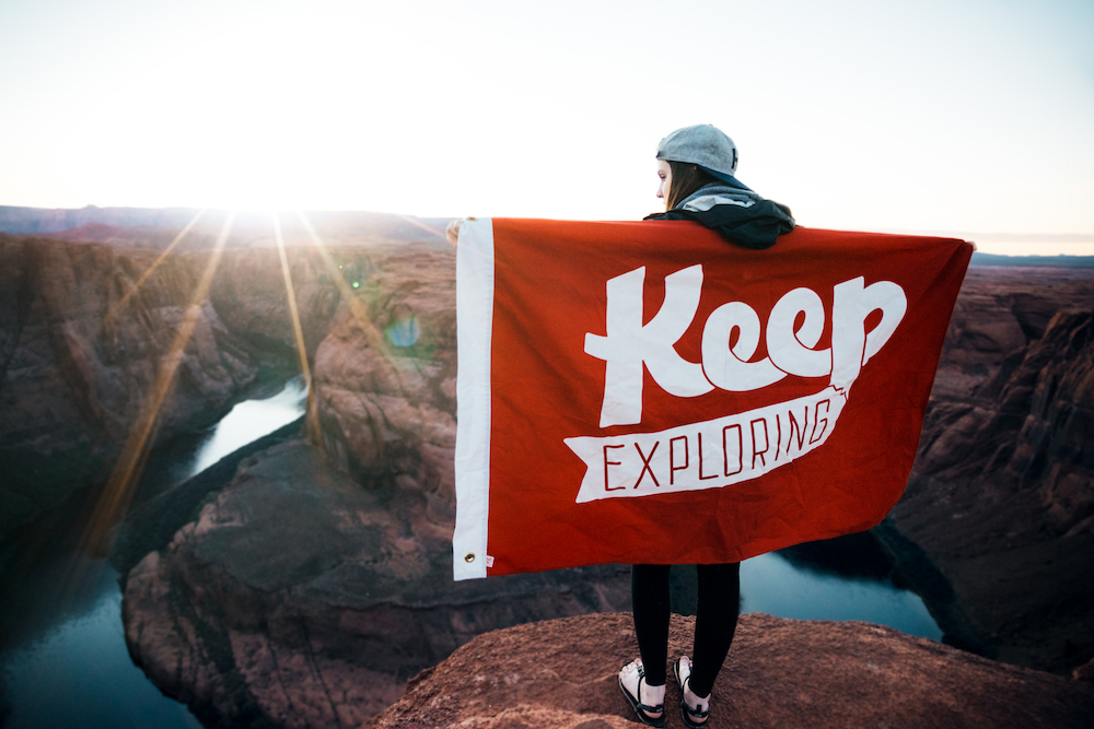 "image of a man on a mountain top with a flag that reads ""Keep Exploring"""