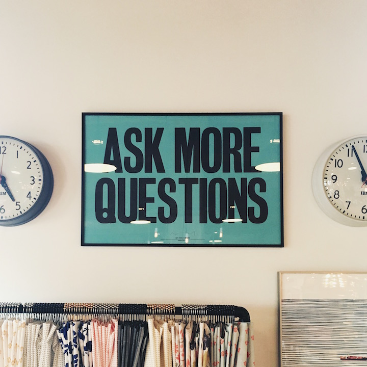 """ask more questions"" sign between two clocks"