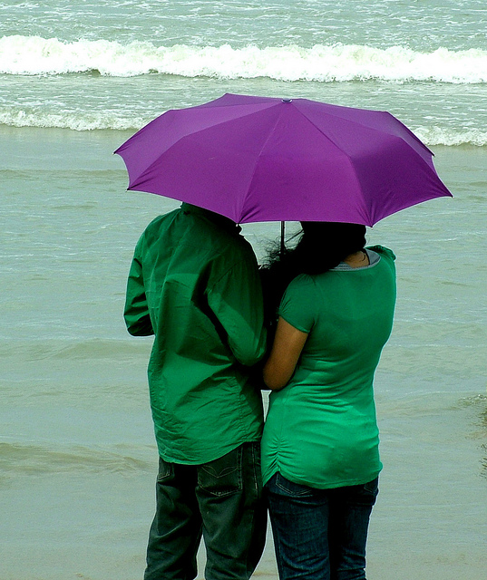Image of two people under an umbrella