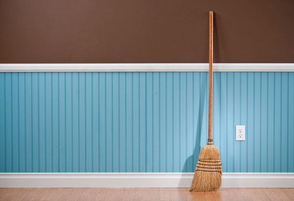 Image of a broom leaning against a blank wall