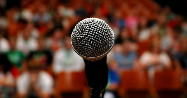Image of a microphone, facing a full audience