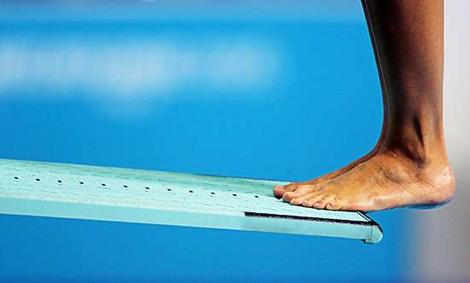 Image of a man standing on the end of a diving board