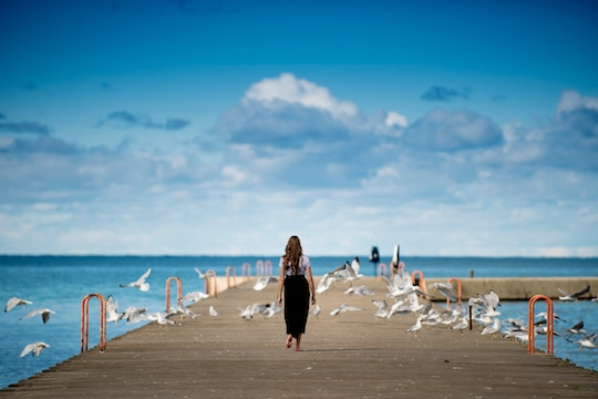 Image of a woman walking among birds