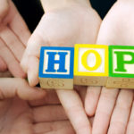 "Hands holding letters spelling ""HOPE"""