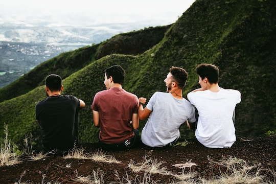 Image of four men sitting on the edge of a mountaintop