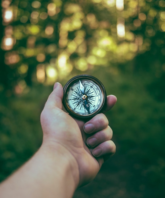 Image of a hand holding a compass