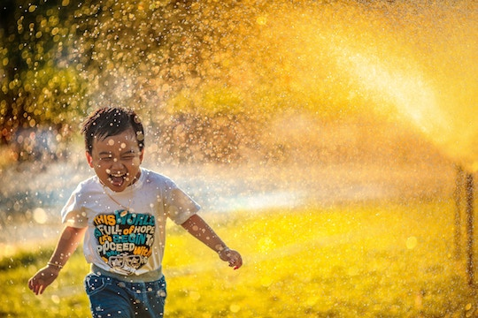 Image of a small boy running through sunlighted sprinkler