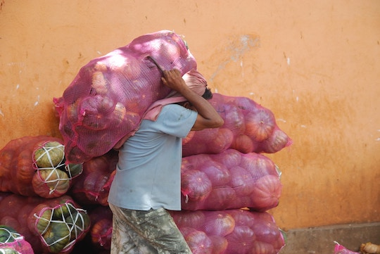 Image of a man carrying a heavy sack