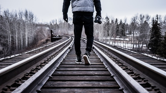 Image of a man walking down a railroad track