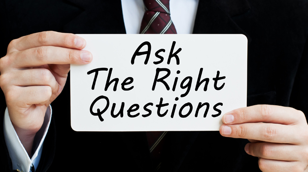 "Image of man holding placard saying ""Ask the right questions"""