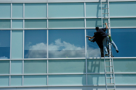 Image of man washing windows on a tall building