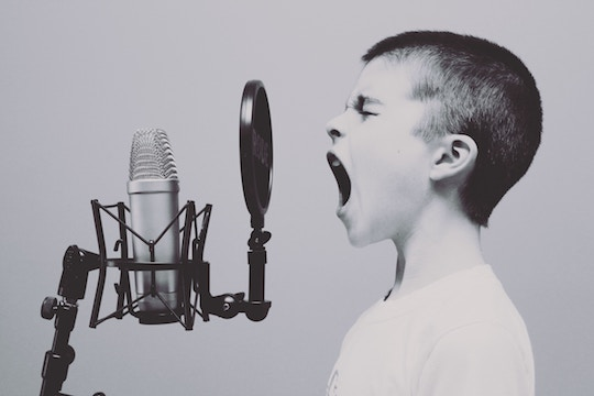 Image of a boy screaming into a microphone