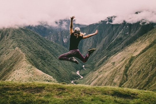 Image of a man leaping for joy on a mountain top