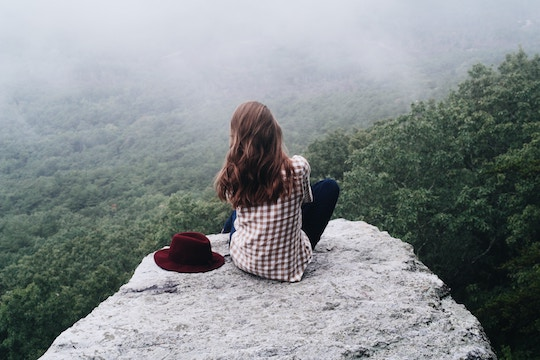 Image of woman sitting on a mountaintop