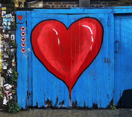 Image of a blue barn door with a large red heart painted on it
