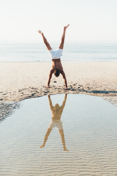 Image of a man doing a handstand on the beach