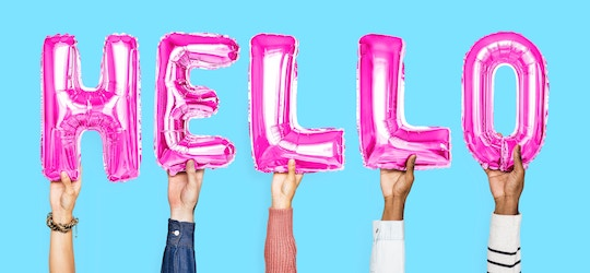"Image of hands holding up pink balloons spelling ""hello"""