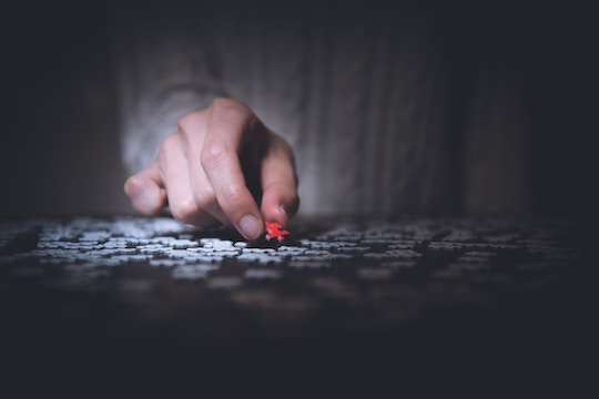 image of a hand placing a piece in a jigsaw puzzle
