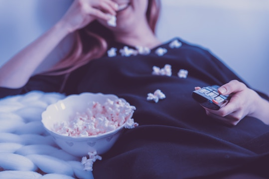 Image of a woman watching TV and eating popcorn
