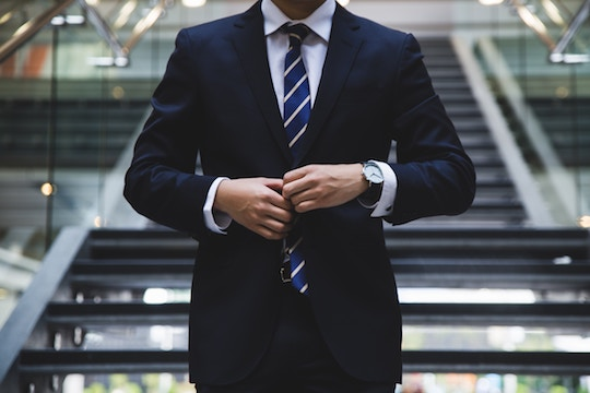 Image of a man buttoning his suit jacket