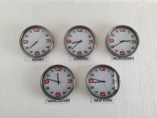 Image of five clock on a wall, showing different time zones