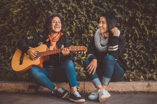 Image of two women playing guitar and singing while sitting on a curb