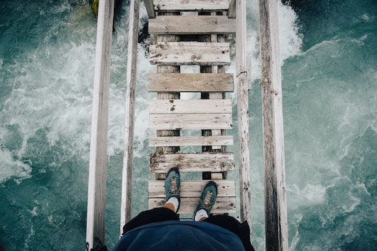 Image of a person standing on a rickety wood bridge over rapids