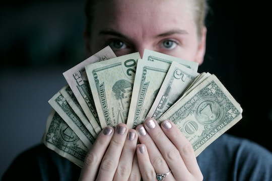 Image of a woman holding a fan of American money