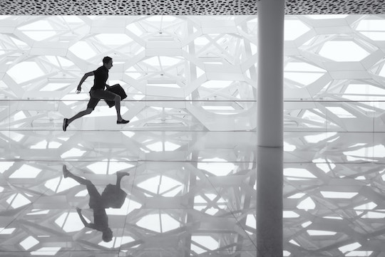 Image of a man running across a glass floor