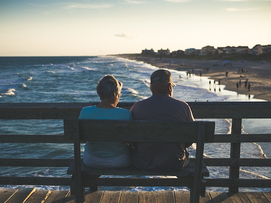 Image of an older couple sitting on a bench overlooking the ocean