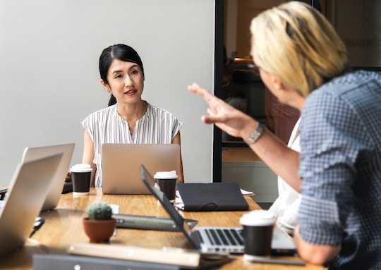 Image of two people talking at a business meeting