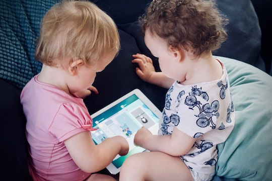 Image of two toddlers playing with a computer