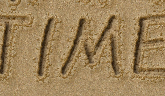 "Image of ""Time"" written in the sand"