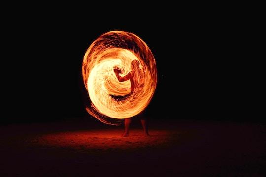 Image of a man spiraling a wand of fire